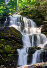 cascades of big waterfall in forest. beautiful summer scenery at sunrise. beams of light on water splashes. nature power and beauty concept