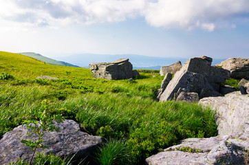 beautiful morning scenery in mountains. rocks among the grass. cloudy sky over the mountain ridge
