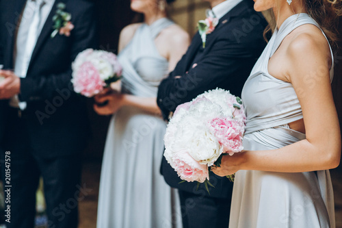 03644874685 gorgeous bridesmaids with peony bouquet and stylish groomsmen posing in  room for photo. luxury wedding couple with friends in church. group of  elegant ...