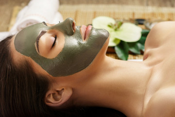 Spa Clay Mask. Woman with clay facial mask   in beauty spa. Skin