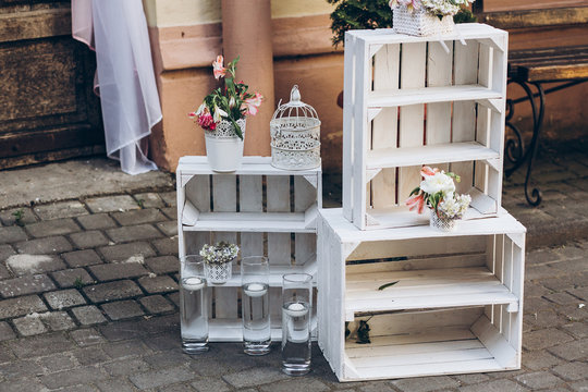 rustic wedding photo zone.  white boxes with flowers and candles at stylish wedding photo booth on background wooden barn doors with fabric and. shabby chic. luxury arrangments