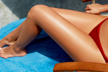 Closeup on female Hand applying sunscreen creme on Leg. Skincare. Sun protection sun cream, on her smooth tanned legs.