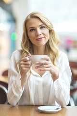 Young blonde sitting in a cafe, drinking coffee and looking into the camera sarcastically