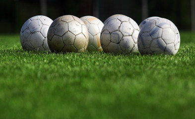 Many soccer balls on grass