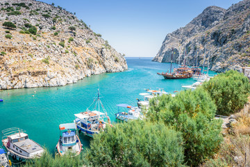 Beautiful sunny coast view to the greek blue sea with crystal clear water beach with big tourist boat cruising around pier in Vathys Bay , Patmos Island, Kos, Dodecanese Islands, Greece