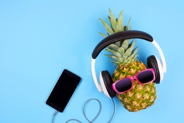 Fashion pineapple with sunglasses and headphones. Top view against a blue background.