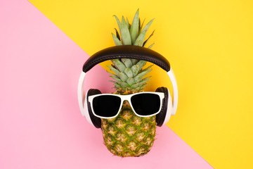 Hipster pineapple with sunglasses and headphones. Top view against a yellow and pink background. Minimal summer concept.