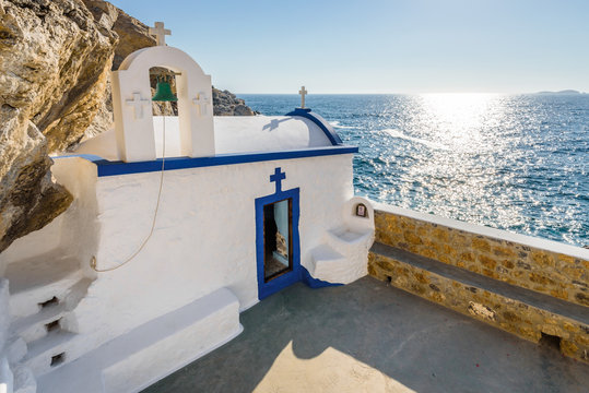 Beautiful blue white greek church called Agios Georgios situated at the cliffs reachable by steps and views to the mediterranean sea and the stormy bay on Telendos Island, Kalymnos, Dodecanese, Greece