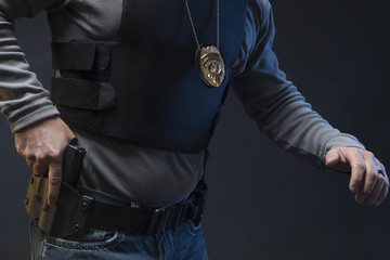 Law Enforcement Agent Studio Shoot with hand on gun.
