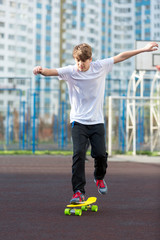 cute young sport boy skating on yellow skateboard and has a good time on his free time on weekend, holidays. healthy sport lifestyle concept for kids