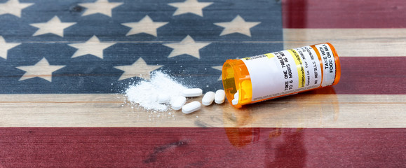 Open prescription bottle of crushed and whole opioid pain killer tablets on USA rustic flag in background