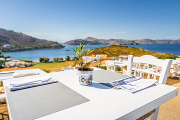 Your table is already reserved at the greek mediterranean sea behind crystal clear blue water and a beautiful coastal aegean bay with fishermen boats cruising, Patmos Island, Kos, Dodecanese, Greece