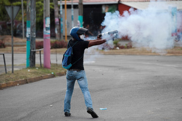 A demonstrator fires a homemade mortar towards riot police during a protest over a controversial reform to the pension plans of the Nicaraguan Social Security Institute in Managua