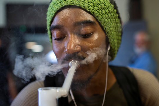 Jeremy Gaines exhales while using a full spectrum oil vaporizer at the new Magnolia cannabis vape lounge in Oakland
