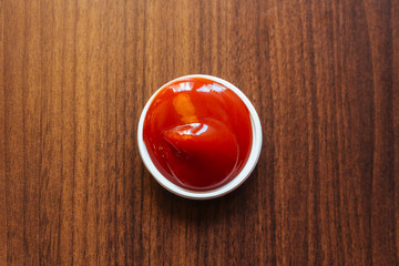 A cup of ketchup place on wooden table.