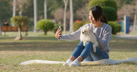 Woman taking selfie by mobile phone with her dog