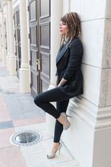 Beautiful woman wearing business suit and high heeled shoes with tattoos and dreadlocks leaning against a wall