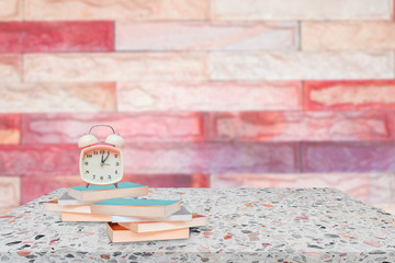 alarm clock and books on stone shelf in library school concept with brick wall blur background copy space add text