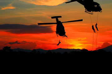 Silhouette Soldiers rappel down to attack from helicopter with sunset and copy space add text ( Concept stop hostilities To peace)