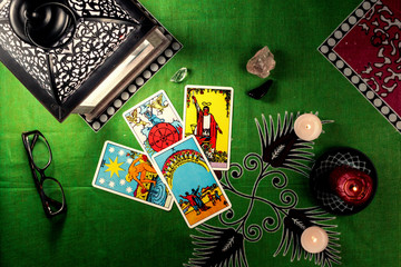 Divination by tarot cards. On a background of a green tablecloth with burning candles.
