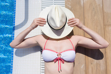 Woman lying next to a swimming pool with hat covering her face
