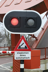 "Red light at bridge for cyclist with tekst ""slagbomen dalen automatisch"" in dutch which means ""barrier will go down automaticly"""