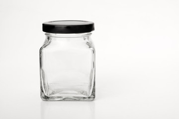 Square empty glass jar with black lid.