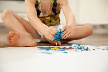 The boy draws his hands with gouache paints while sitting on the floor.