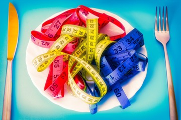 plate with colored metrics and cutlery. diet and slimming concept