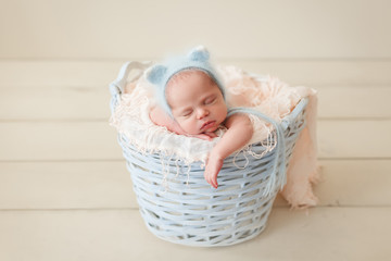 Newborn sleeping in a wicker basket in a blue fluffy knit kitty hat on a pink props on a beige wooden floor