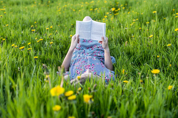 Girl lying in grass reading a book