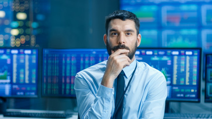 Stock Market Top Trader Thinking Hard on Selling Stocks at the Best Time. Behind Him People Working and Monitors Show Graphs and Ticker Figures.