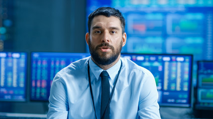 Professional Stock Market Trader Charismatically Talks into the Camera. Behind Him Computer Screens with Ticker Numbers, Data, Graphs.