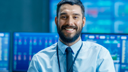 Handsome Stock Market Trader Smiles into the Camera. Behind Him Computer Monitors Showing Ticker Numbers and Graphs.