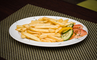 Fried potatoes with peppers, tomatoes and cucumber
