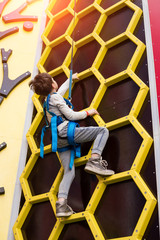 Climbing a mountain represents a chance to be briefly free oneself of the small concerns of our common lives! Young little child enthusiastically climbing the mountain wall in the playing room.