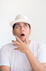 Asian man wear white hat with shock expression emotion at white wall background.looking up.