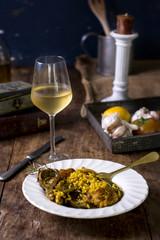 Plato de paella con vino en una mesa de madera