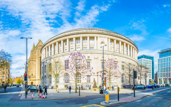 People are passing in front of the Manchester central Library, England