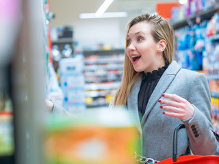 Surprised caucasian girl in supermarket buying products