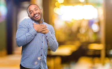 African american man with beard having charming smile holding hands on heart wanting to show love and sympathy at night