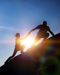 The joint work teamwork of two people man and girl travelers help each other on top of a mountain climbing team, a beautiful sunset landscape. The silhouettes on top of a mountain