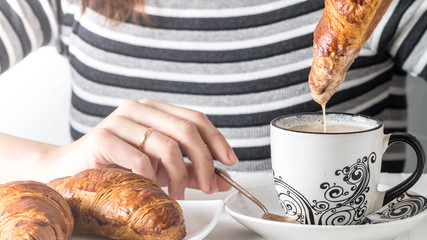 Close-up view of a hand dipping a croissant in a coffee