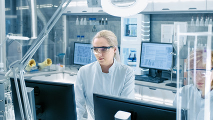 Shot of Young Laboratory Assistant Walking to Her Workplace. Female Scientists of Different Age Working in this State of the Art Laboratory.