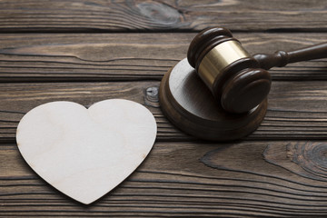 a judge hammer, a heart shape on a wooden background. family law.