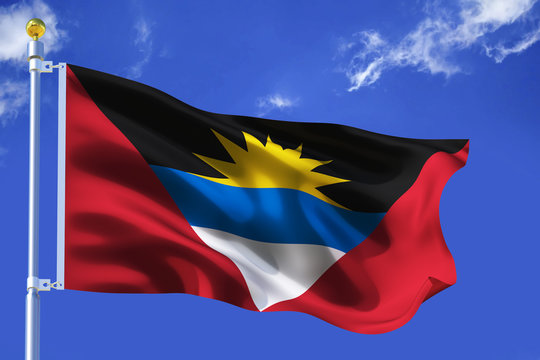 The silk waving flag of Antigua and Barbuda with a flagpole on a blue sky background with clouds .3D illustration..