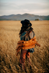 Boho nomads girl in field at Sunset