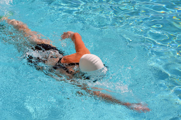 Angled overhead view of a woman swimming laps in a condo swimming pool.