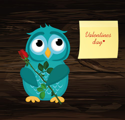 Cute blue owlet waiting to give a  of flower pink rose
