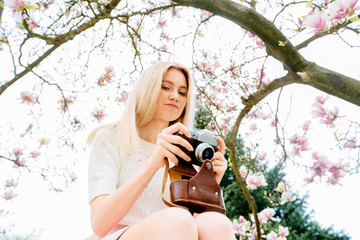 Young woman traveler take photos by camera under magnolia blossoms tree. Women traveler use retro camera take a photo sakura in full blooming.